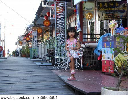 Georgetown, Penang, Malaysia, November 13, 2017: Girl On A Street In Tan Jetty, The Floating Town Of