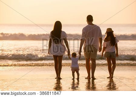 Family Of Four Peoples In White Are Standing And Relaxing At Sunset Sea Beach