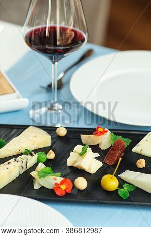 Closeup On Assorted Spanish Cheese Platter With Red Wine On The Blue Table