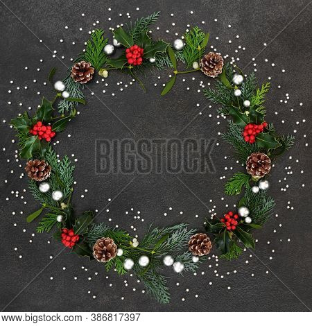 Abstract Christmas & winter wreath with holly, mistletoe, cedar cypress fir leaves, pine cones & silver balls on grunge grey background. Xmas & New Year composition.
