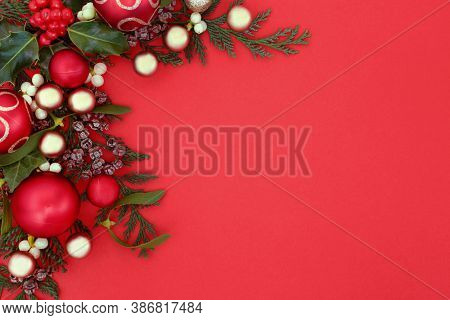 Christmas background border with bauble decorations, holly & winter greenery of mistletoe, ivy, & cedar cypress fir on red. Xmas New Year composition for the festive season. Top view, copy space.