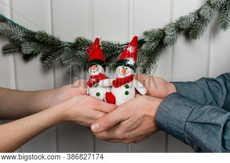 Two Cute Toy Snowmen In Male And Female Hands Crossed Together. Hand Made Snowman In Hat And Scarf R