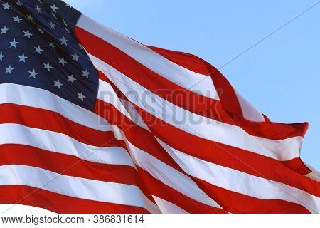 Large American Flag Gently Waving In The Wind. American Flag Waving Under A Blue Sky With Clouds. Re