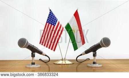 3d Illustration. Microphones And Tajik, Usa Flags Pair On A Desk Over Defocused Background