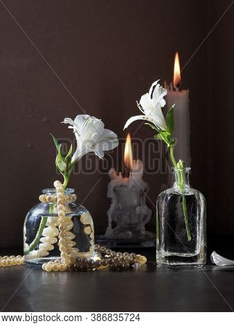 Retro Style Still Life With Alstroemeria Flowers In Small Vintage Bottles, Candlesticks With Burning
