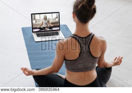 Close Up Of Young Sporty Woman Practicing Yoga Online With Laptop At Home. Yoga Instructor Conductin