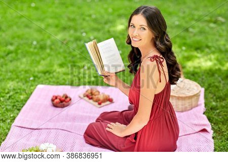 leisure and people concept - happy smiling woman sitting on picnic blanket and reading book at summer park