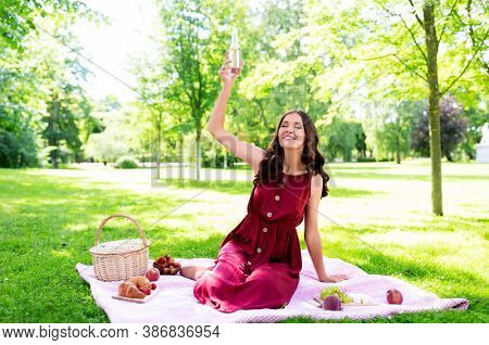 leisure and people concept - happy smiling woman with picnic basket and fizzy drink in bottle sitting on blanket at summer park