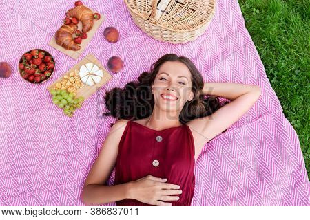 leisure and people concept - happy smiling woman with picnic basket and food lying on blanket at summer park
