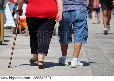 Old Couple Walking On A City Street In A Crowd Of People, Rear View On The Legs. Elderly Man And Wom