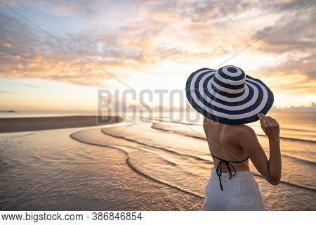 Woman In Top Bikini And White Long Pant Wearing Hat On The Beach With A Beautiful Sunrise Or Sunset