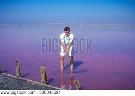 Brunet Man Relaxing On Pink Salty Sivash Lake Near Azov Sea, Colored By Microalgae Dunaliella Salina