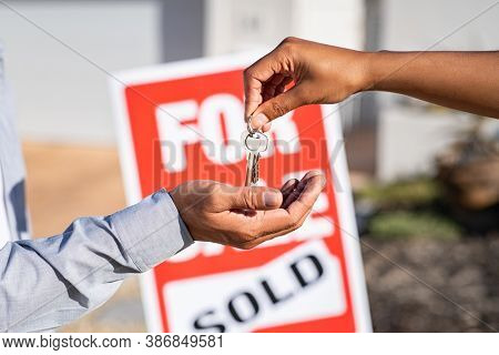 Saleswoman giving home keys to new property owner. Close up of real estate agent hand giving house keys to man. Agent giving apartment key to new owner after putting the word sold on for sale sign.