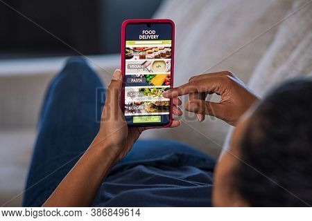 Woman lying on couch using food delivery app on smartphone. Close up of african woman hands holding cellphone and ordering food online.