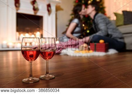 Two Glasses Of Sparkling Wine In Front Of Warm Fireplace. Cozy Relaxed Romantic Atmosphere Near Fire