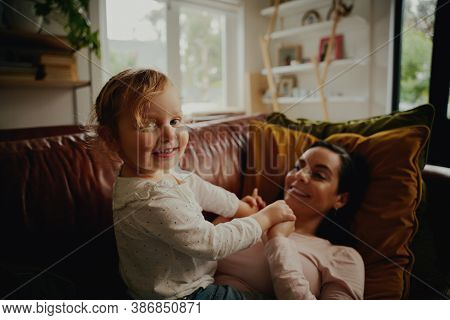 Portrait Of Excited Little Child Playing With Mother Lying On Couch At Home During Covid-19 Lockdown