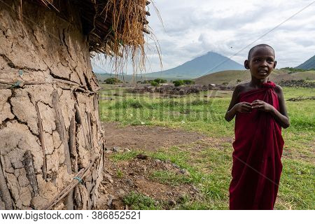 Engare Sero. Tanzania - January 2020: Indigenous Maasai Boy Near The Clay Hut In Traditional Village