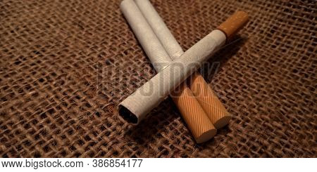 Three White Cigarette On Brown Sack Mat Background, Pack Of Cigarettes, Close-up Of A Cigarette