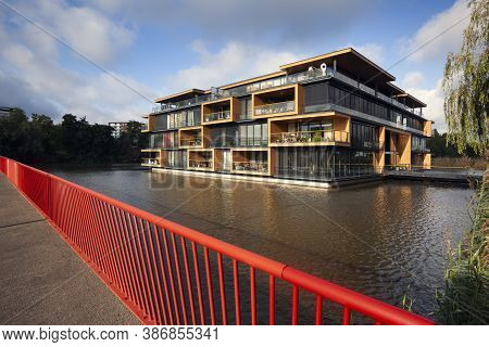 Apartment Building Built In Water In Rotterdam Seen From A Bridge With Red Railing In The Netherland