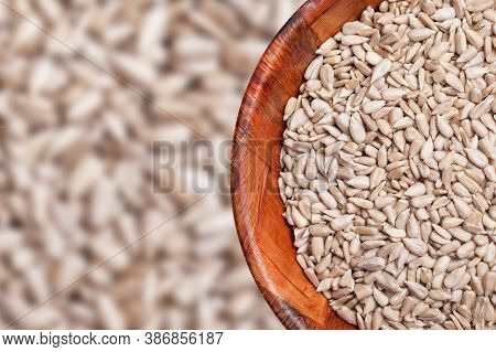 Hulled Sunflower Seeds In Wooden Bowl. Round Kitchen Container Filled With No Shell Sunflower Seeds