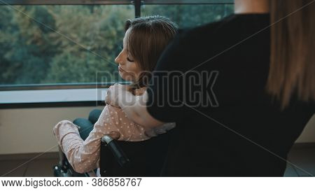 Young Disabled Woman Looking Over The Shoulder At Her Carer. High Quality Photo