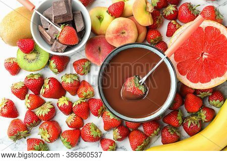 Fondue Fork With Strawberry In Bowl Of Melted Chocolate Surrounded By Other Fruits On White Marble T