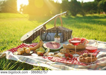 Picnic Blanket With Delicious Food And Drinks Outdoors On Sunny Day