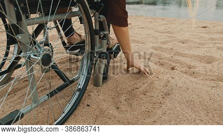 Close Up, Hand Of Disabled Person In The Wheelchair Playing With The Sand On The River Coast. Vacati