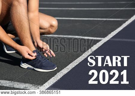 Sporty Man Tying Shoelaces In Front Of Starting Line With Text Start 2010 At Stadium, Closeup