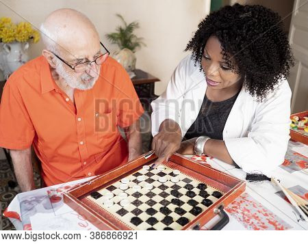 Horizontal Portrait Of An African American Medical Assistant Playing A Board Game With An Ederly Cau