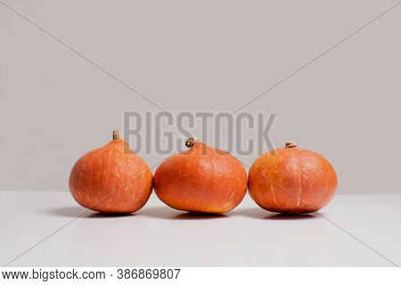 Three Orange Pumpkins On White Table In Front Of Gray Background Side View With Copy Space. Autumn H