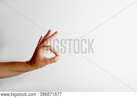 Female Hand Shows Okay Gesture From Side, On White Background With Free Space For Text