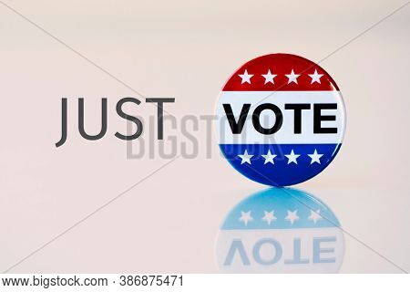 closeup of the word just and a vote badge for the United States election, forming the text just vote on a pale brown background