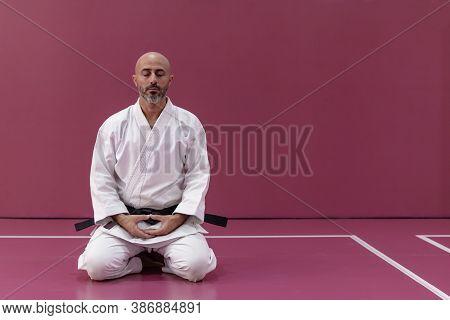 Karate Master With Black Belt Rank, In Meditation Position In His Dojo Or Martial Arts School