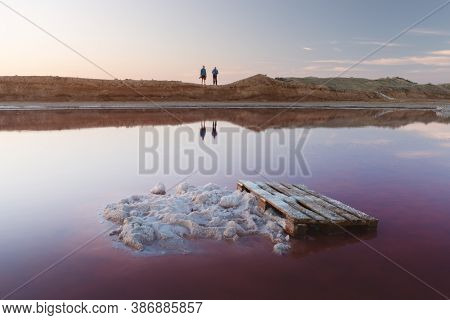 Salt crystals in pink water salt lake in Ukraine, Europe. Two photographers on background. Landscape photography