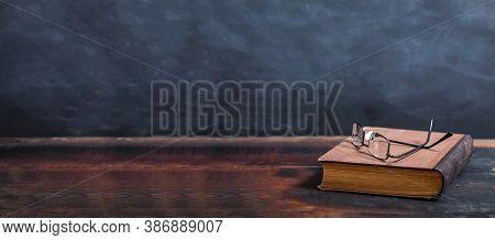 Vintage Old Books And Eyeglasses On Blackboard Background, Copy Space