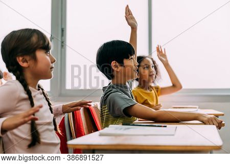 Elementary Age Asian Student Boy Raised Hands Up In Q And A Class. Diverse Group Of Pre-school Pupil