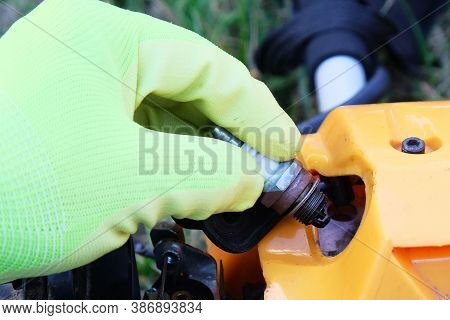 Defective Spark Plug On  Background Of Grass Trimmer,  Hand In  Glove Holds  Close-up, Repair And Ma