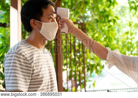 Close Up Hand Using Medical Digital Infrared Thermometer On A Young Man In Face Mask To Check And Mo