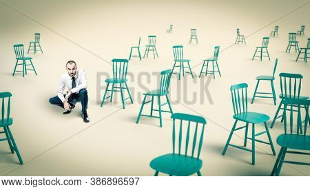 businessman in a crouched position, many chairs around him.