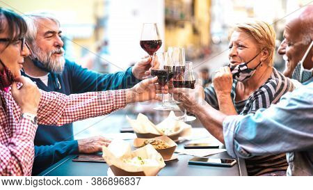 Senior Couples Toasting Red Wine At Restaurant Bar With Face Masks - New Normal Lifestyle Concept Wi
