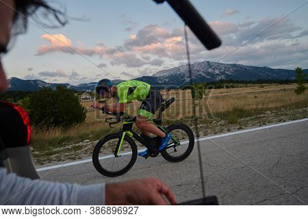cinematographer with professional cinema camera taking sport action shot  from moving car of triathlon athlete who riding bike on low traffic country road