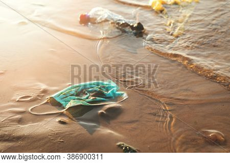 Medical Face Mask And Plastic Waste In The Water On Sea Coast. Environment Pollution Since Coronavir