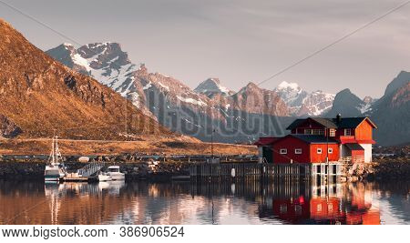 Lofoten Island, Norway, Fishing boats and Traditional Norwegian Rorbuer Cabins At Midnight Sun With Mountain In Background, Lofoten Island, Ramberg, Norway