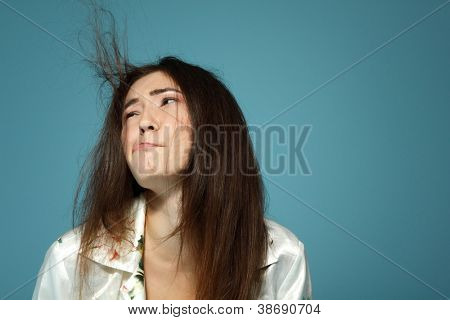 Funny teen girl has problem with her hair in the morning. Over blue background.