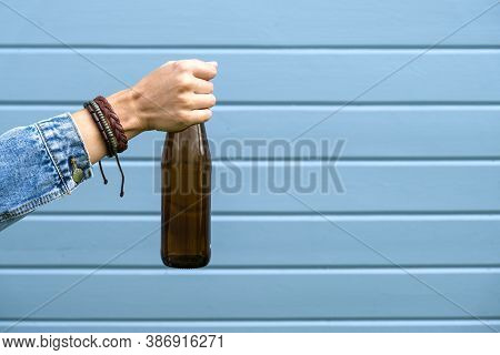 A Female Hand Dressed Punk, Infirmal Holding A Bottle Of Beer Against Blue Wooden Plank Wall, Abuse