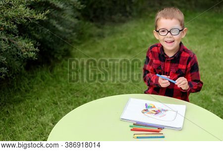 A Little Boy Drawing A Picture In The Garden (outdoors). Wearing Glasses And An Eye Patch (plaster,