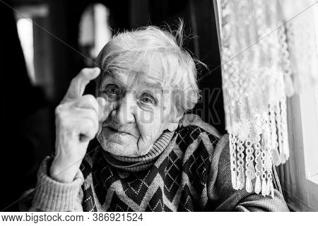Portrait of an elderly woman indignantly wags her finger. Black and white photography.