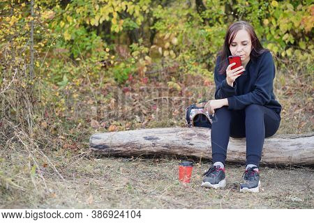 Close Up Of Young Woman Sitting On Log, Browsing Mobile Phone And Drinking Coffee. Adult Brunette Re