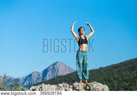 Girl Practices Yoga On Top Of The Mountain, Woman Performs Asanas Standing On A Large Stone Against